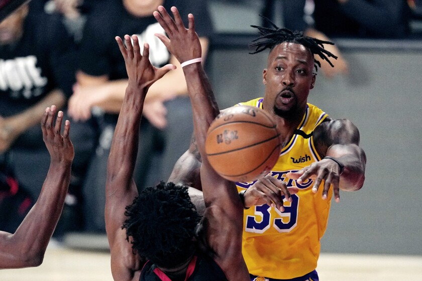 Lakers center Dwight Howard passes the ball while under pressure during the Lakers' win in Game 1.