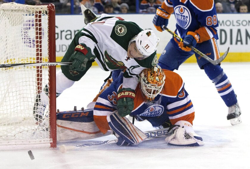 Minnesota Wild ' Zach Parise (11) crashes against Edmonton Oilers goalie Cam Talbot (33) as he dives for the puck during the first period of an NHL hockey game Thursday, Feb. 18, 2016, in Edmonton, Alberta. (Jason Franson/The Canadian Press via AP)