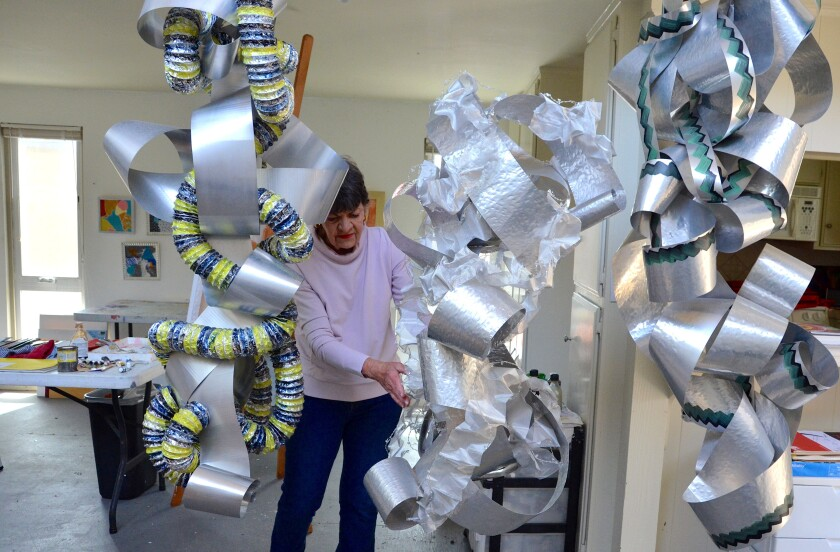 Mary Chabre stabilizes one of her large metal sculptures that hang in her Balboa studio on April 14, 2021.