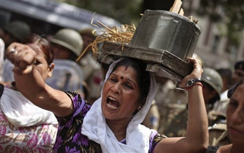 An activist of India's main opposition Bharatiya Janata Party (BJP) shouts slogans as she carries an old cooking stove on her head during a protest in New Delhi, India, Saturday, Sept. 15, 2012. India's beleaguered government faced angry protests from its political allies as well as the opposition