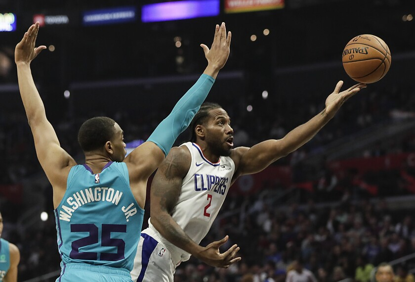 Clippers forward Kawhi Leonard scoops a shot past Charlotte Hornets forward PJ Washington.