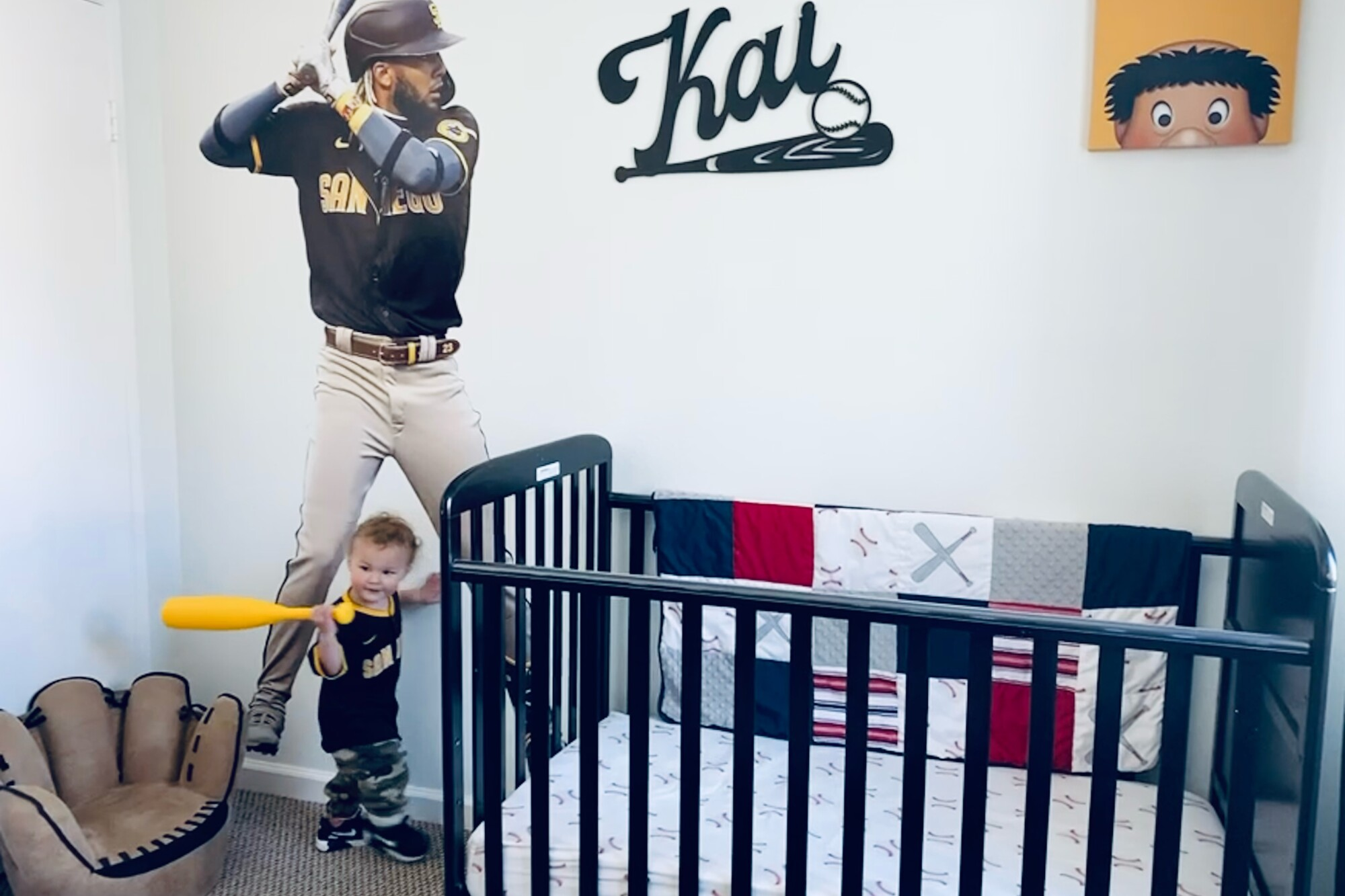 Kai Mac Riley, who will be 2 in June, stands in front of 7-foot poster of Fernando Tatis Jr. in his San Diego room.