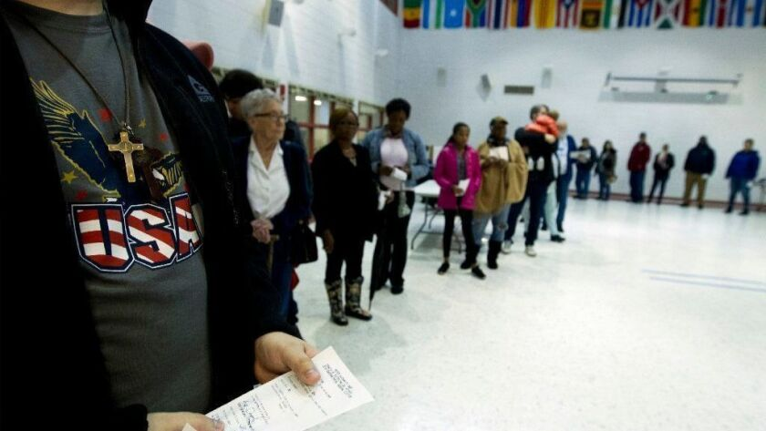 People wait in line Tuesday at a polling place in Silver Spring, Md.