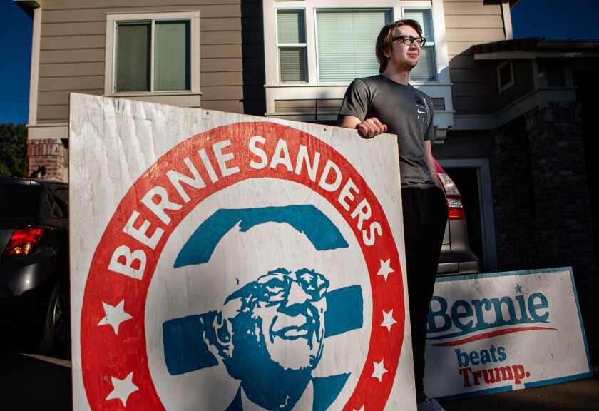 Ben Albrecht, a former Bernie Sanders, supporter poses for a portrait with his Bernie Sanders for President.