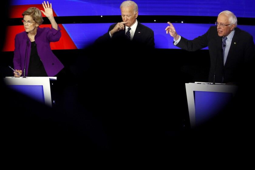 On Jan. 14, 2020, Sen. Elizabeth Warren and Sen. Bernie Sanders raise their hands to answer a question as Joe Biden pauses.