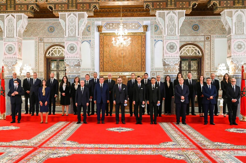In this photo released by the Royal Palace, front row Morocco's King Mohammed VI, center, accompanied by the Crown Prince Moulay El Hassan, 4th right, and his brother Prince Moulay Rachid, 5th right, poses with all members of the new government of Morocco at the Royal Palace in Fez, Morocco, Thursday, Oct. 7, 2021. 4th left is the new prime minister Aziz Akhannouch the president of the National Rally of Independents party (RNI), winner of the legislative elections. (Moroccan Royal Palace via AP)