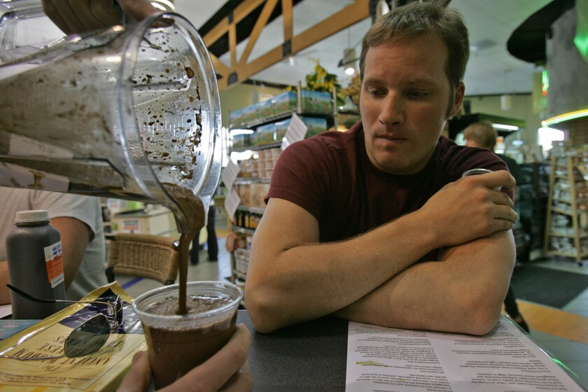 Matt Neely watches as his ice blended maca drink is poured at the tonic bar at Erewhon Natural Foods Market in Los Angeles