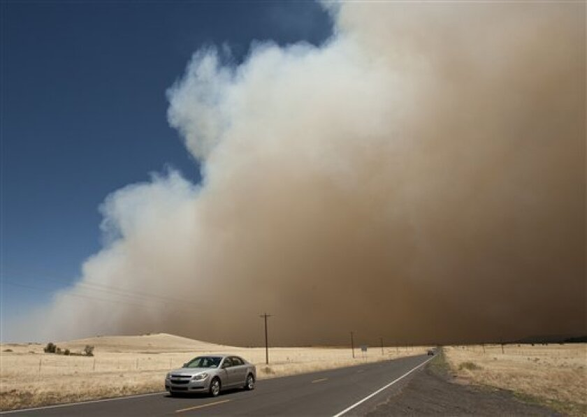 A car drives west on highway 260 away from the Wallow fire as it burns to about one mile from the western edge of Eagar, Ariz. Wednesday, June 8, 2011. Highway 260 has been completely closed between the Arizona towns of Eagar and Show Low. (AP Photo/The Arizona Republic, Rob Schumacher) MARICOPA COUNTY OUT; MAGS OUT; NO SALES