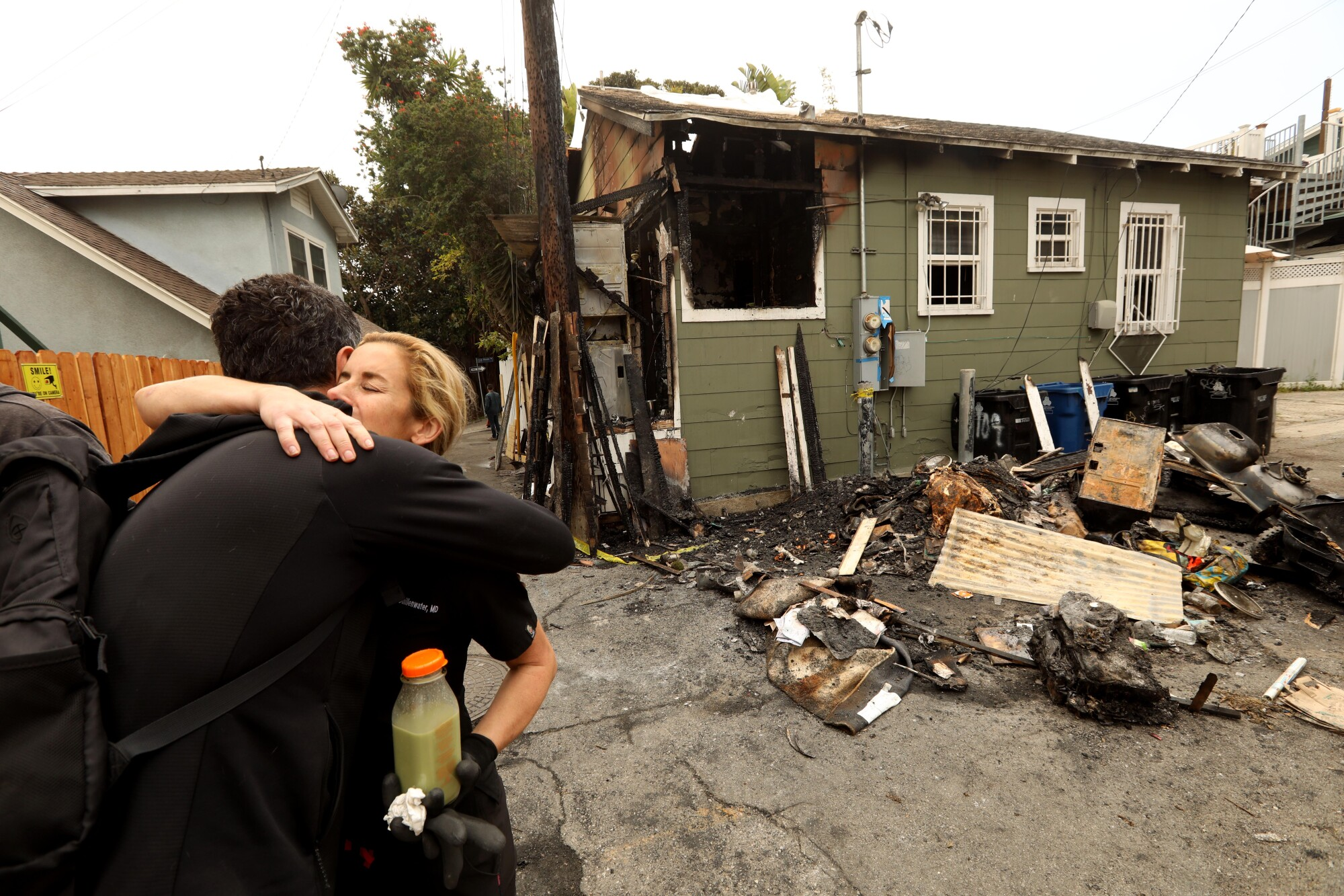 Two people hug outside out of a home with fire damage and debris