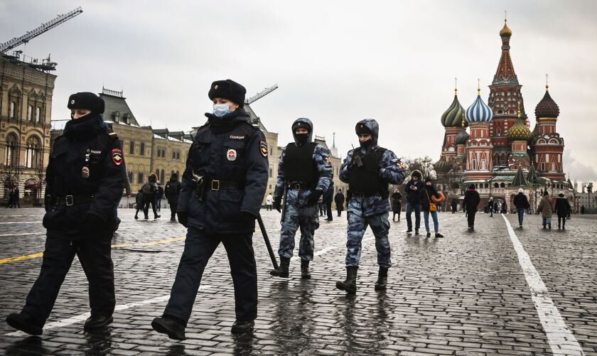 St. Basil's Cathedral is in the background as four officers walk through a lightly populated Red Square.