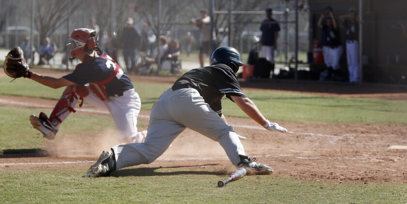 Costa Mesa High's Kyle Anderson dives for home plate against Calvary Chapel during the third inning