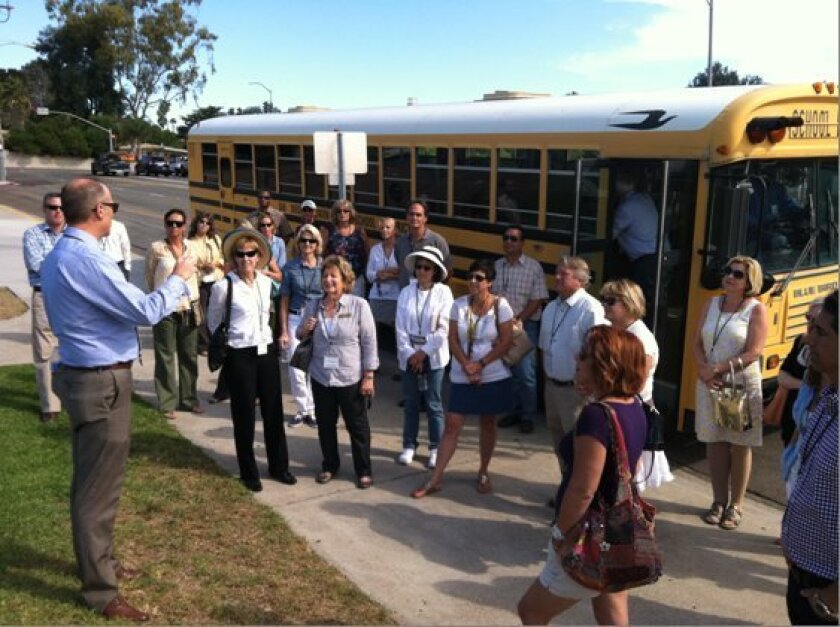 Eric Dill (left), associate superintendent of business services for San Dieguito Union High School District, welcomes trustees and other guests on a tour of school sites being renovated with Prop. AA money.