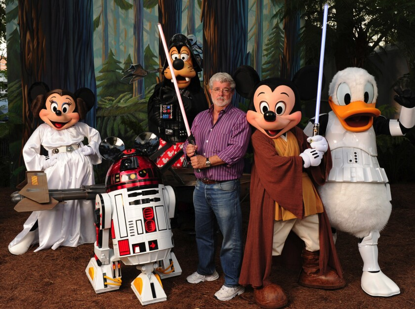 """""""Star Wars"""" creator and filmmaker George Lucas poses with a group of """"Star Wars""""-inspired Disney characters at Disney's Hollywood Studios theme park in Lake Buena Vista, Fla. Some Disney fans believe a Disneyland expansion could include """"Star Wars"""" characters and story lines."""
