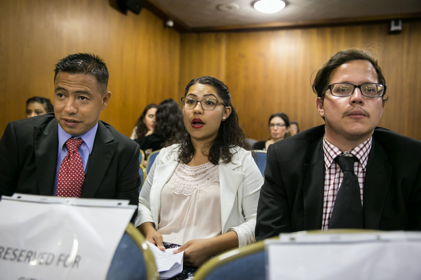 Francisco Medina, left, and Julian Zatarain, right, listens to council members' comments after their appointment as city commissioners at Huntington Park City Hall.