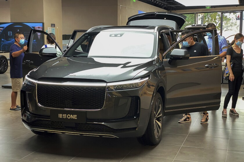 People wearing face masks to help curb the spread of the coronavirus look at a new Chinese-made electric Li One SUV at a dealership in Beijing on Aug. 2, 2020. China's sales of SUVs, minivans and sedans fell 6% last year compared with 2019 after demand plunged due to the coronavirus and rebounded in the second half. (AP Photo/Andy Wong)