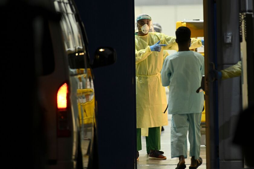 Medical staff wait for COVID-19 patients to be transferred to a temporary hospital in Singapore.