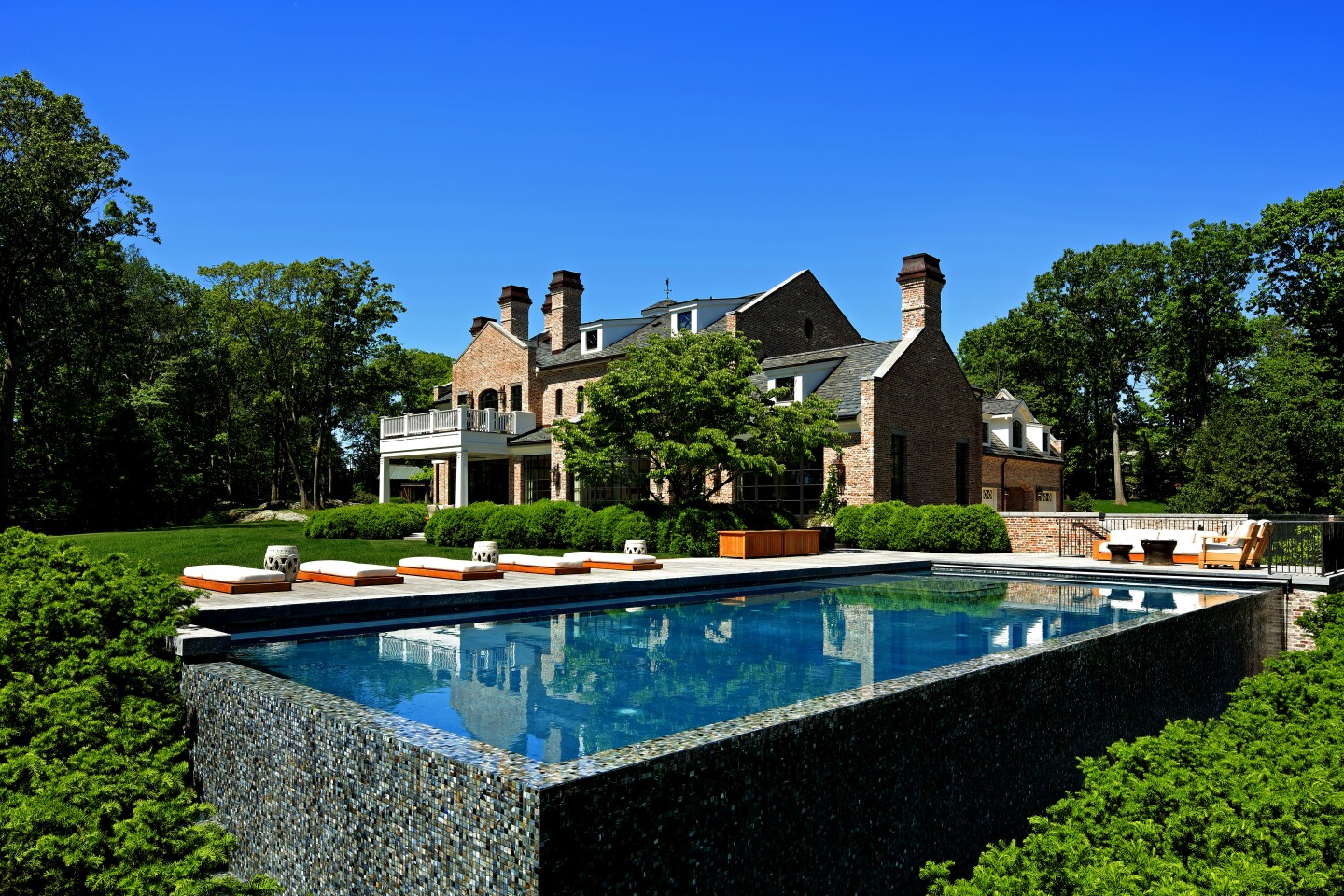 Tom Brady and wife Gisele Bündchen are now asking $33.9 million for their Massachusetts home, down about $6 million from when the five-acre estate first listed for sale last year. The Richard Landry-designed manor features a classic brick exterior, modern amenities and a country-inspired kitchen. The skylight-topped breakfast room features a wall of steel-framed doors and windows that takes in leafy views. A barn-inspired guest house accompanies the 10,000-square-foot main house. Elsewhere on the grounds is a zero-edge swimming pool.