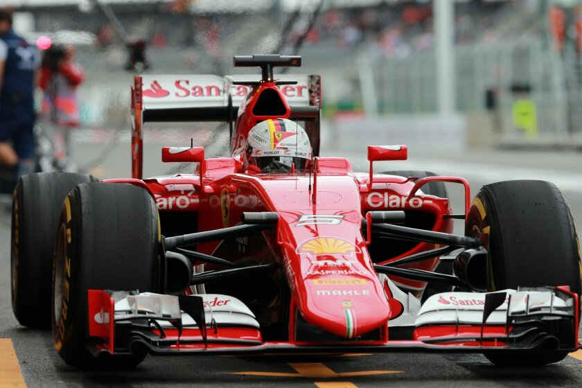 Ferrari driver Sebastian Vettel of Germany arrives at the pits during the third practice session for the Formula One Mexico Grand Prix auto race at the Hermanos Rodriguez racetrack in Mexico City, Saturday, Oct. 31, 2015. (AP Photo/Christian Palma)