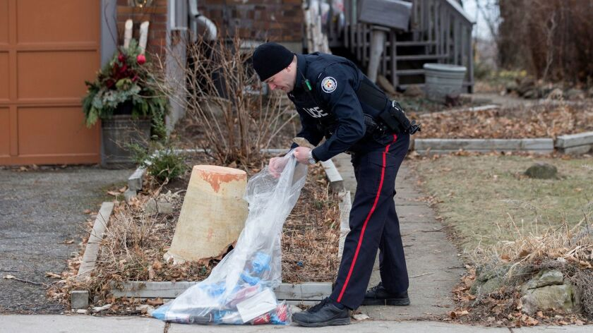 A police officer investigates outside a Toronto home serviced by landscaper Bruce McArthur, who is accused of killing at least five people and is suspected of more slayings.