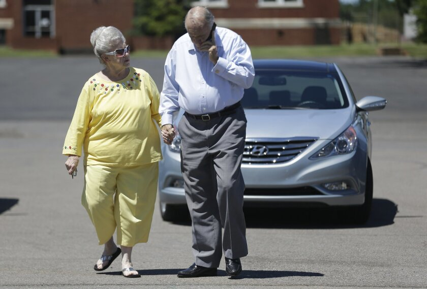 Talladega Mayor Larry Barton walks with his wife, Mary Barton during an election, Tuesday, Aug. 25, 2015, in Talladega, Ala. Voters will decide whether their mayor, who was re-elected despite a federal conviction and is recovering from an assault, will be back in office for a fifth term. (AP Photo/Brynn Anderson)