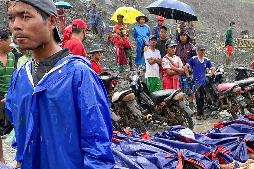 People gather near the bodies of victims of a landslide in northern Myanmar.