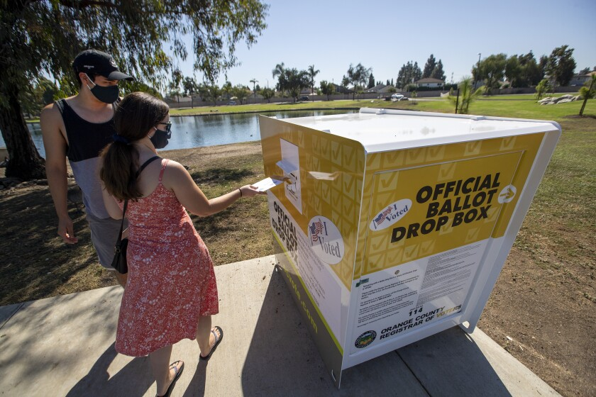 A man and a woman put their ballots into a drop box at Carl Thornton Park in Santa Ana in last year's election.
