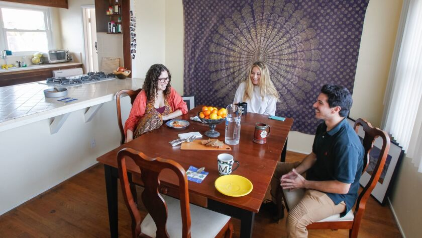 Moishe House residents Chelsea Bradford-Hall, left, Miranda Kalman, and Moses Wosk hang out in their house in Oceanside on Thursday.
