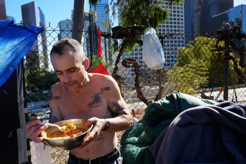 FILE - This Tuesday, Jan. 26, 2016 file photo Eddie, 51, a homeless man who would only give his first name and lives in a tent on the street in downtown Los Angeles. Los Angeles city and county officials have approved sweeping plans to deal with homelessness at a cost of billions over a decade. The