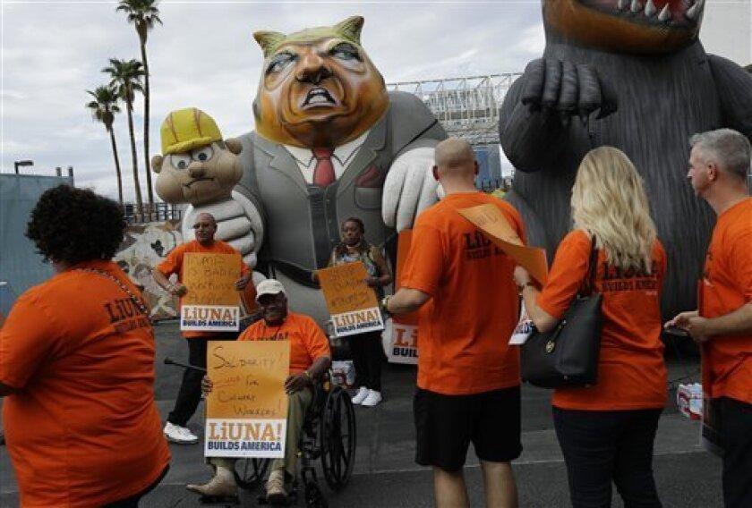 Fotografía de archivo del 21 de septiembre de 2016 muestra miembros del Sindicato Internacional de Trabajadores de Norteamérica y miembros del Sindicato Culinario caminando frente a una figura inflable con la imagen de Donald Trump durante una protesta afuera del hotel Trump International, en Las Vegas.