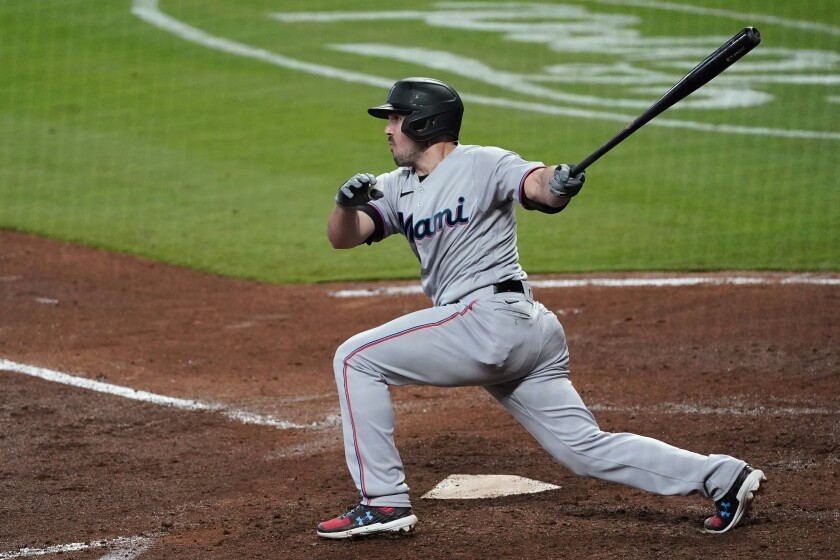 Miami Marlins' Adam Duvall follows through on a two-run double during the fourth inning of the team's baseball game against the Atlanta Braves on Tuesday, April 13, 2021, in Atlanta. (AP Photo/John Bazemore)