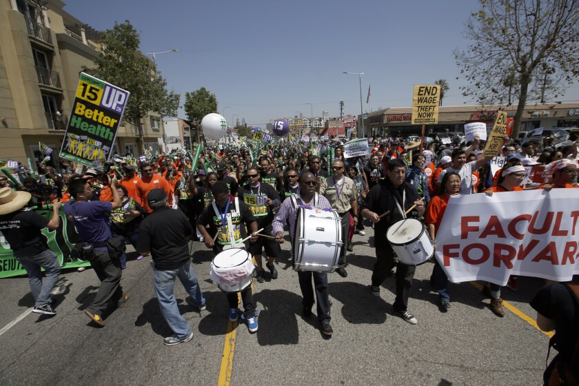 About 1,000 demonstrators -- including union members, fast-food employees and child-care workers -- march for higher wages Wednesday on South Figueroa Street in Los Angeles.