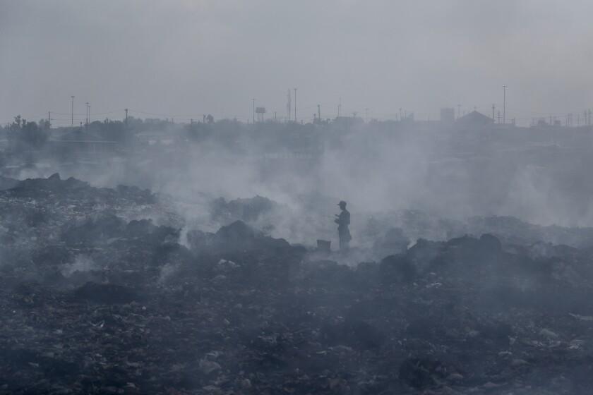 Un hombre cruza una una montaña de basura en medio del humo de fogatas en Dandora, el basural más grande de Nairobi, Kenia, el 7 de septiembre de 2021. (AP Foto/Brian Inganga, File)