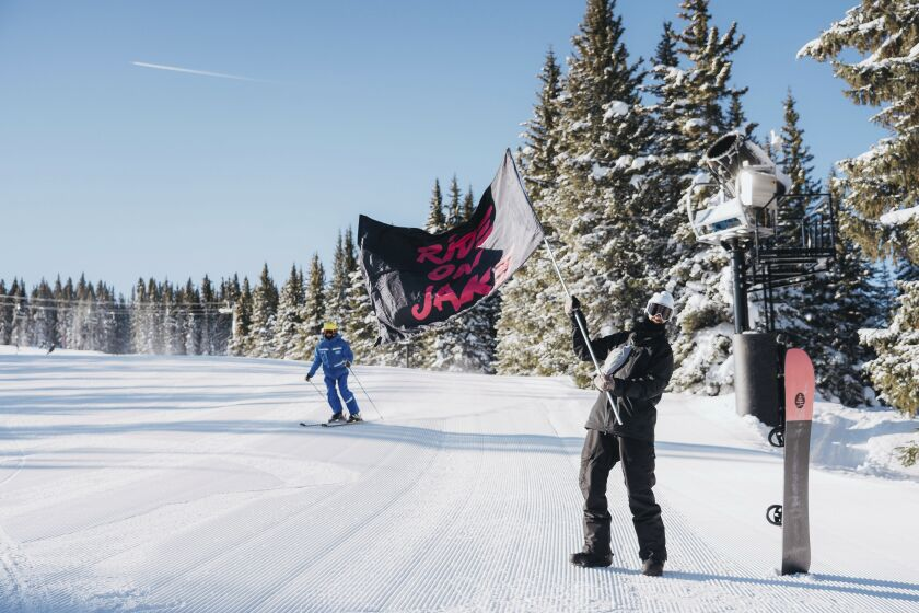 """In a photo provided by Burton, a fan of Jake Burton Carpenter waves one of dozens of """"Ride On Jake"""" flags that dotted the course in Vail, Colo., Friday, Feb. 28, 2020. Skiers and snowboarders alike gathered over the weekend to celebrate Carpenter, who died November 2019 of testicular cancer. It was Carpenter who envisioned what snowboarding could be back in the 1980s and started producing snowboards to help his vision become reality. (Dean Blotto Gray/Burton via AP)"""