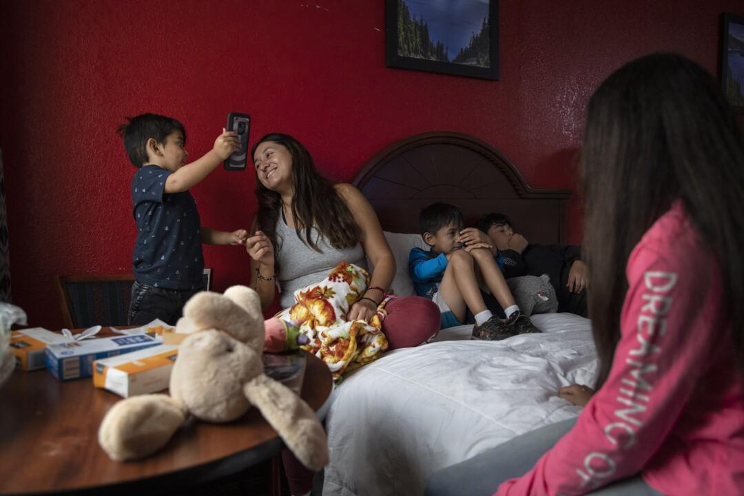 Maritza Macias smiles at Matthew, 2, Emmanuel, 6, center, Leo, 11, and Joanna, 13, in their hotel room.