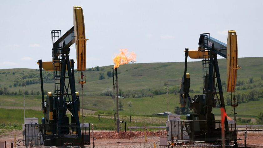 Oil pumps and natural gas burn off in Watford City, N.D. on June 12, 2014.