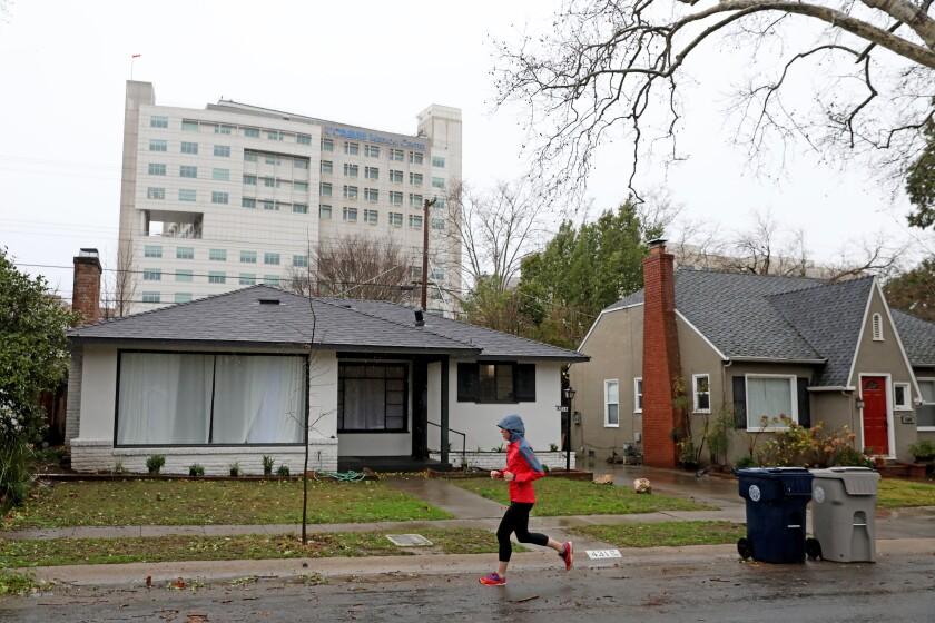 A jogger passes single family homes along the 4300 block of U St. in the Elmhurst neighborhood of Sacramento