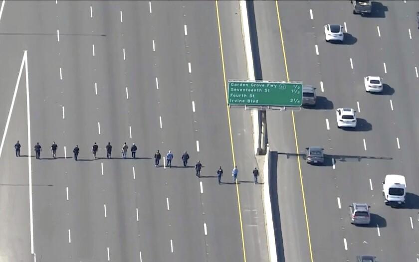 A line of people walk along empty freeway lanes.