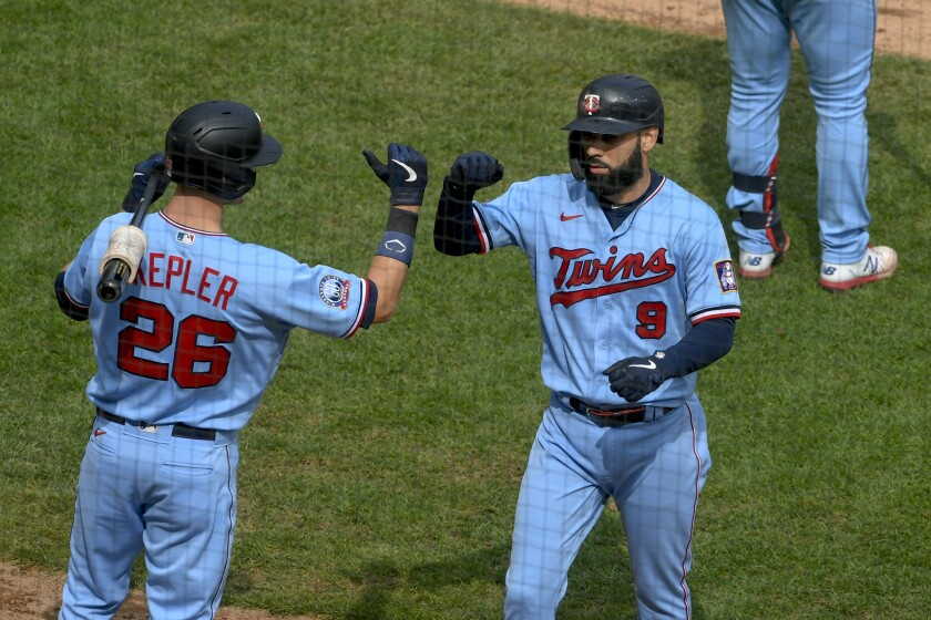 Minnesota Twins designated hitter Nelson Cruz, right, celebrates with Max Kepler after Cruz hit a home run during the third inning of a baseball game Sunday, Sept. 13, 2020, in Minneapolis. (AP Photo/Craig Lassig)