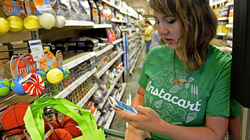 Kaitlin Myers, an Instacart shopper, checks her phone as she shops for a customer at a Whole Foods in Denver in 2014.