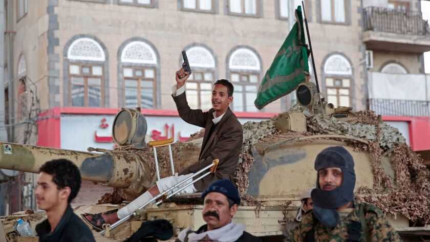 Houthi Shiite fighters guard a street leading to the residence of former Yemeni President Ali Abdull