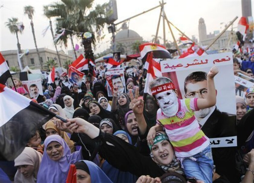 Supporters of Egypt's ousted President Mohammed Morsi wave his posters and national flags as one carries her daughter with a mask of him during a protest in Nahda Square, where protesters have installed their camp near Cairo University in Giza, southwestern Cairo, Egypt, Tuesday, Aug. 13, 2013. Egypt's interim president swore in 20 new provincial governors on Tuesday, a move that reinforces the new leadership's authority and removes all Muslim Brotherhood members previously installed in the post