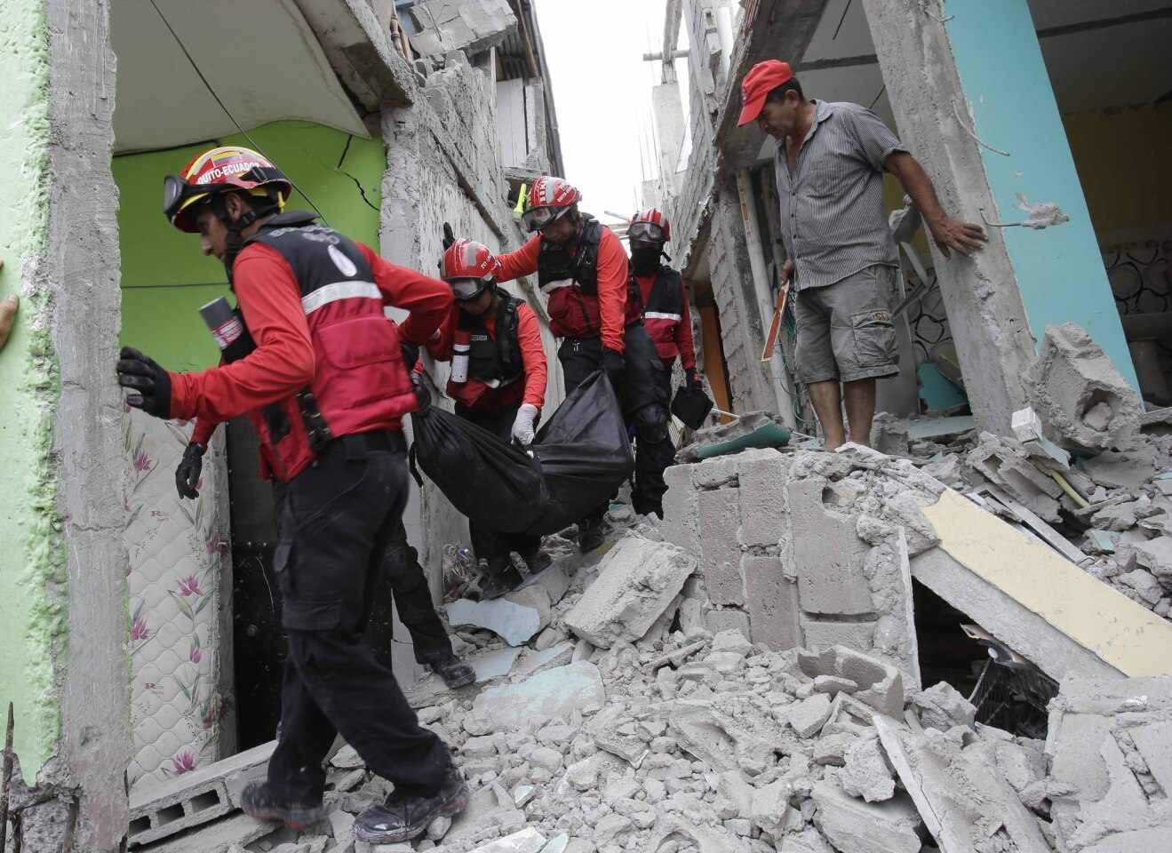Firemen carry a body from a collapsed building in Pedernales, Ecuador. Rescuers pulled survivors from rubble Sunday after the strongest earthquake to hit Ecuador in decades flattened buildings and buckled highways along its Pacific coast.