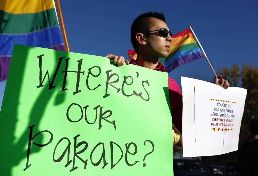 Minh Tran of Westminster holds a sign and gay pride flag as he protests the exclusion of LGBT groups from the upcoming Tet parade in Little Saigon.