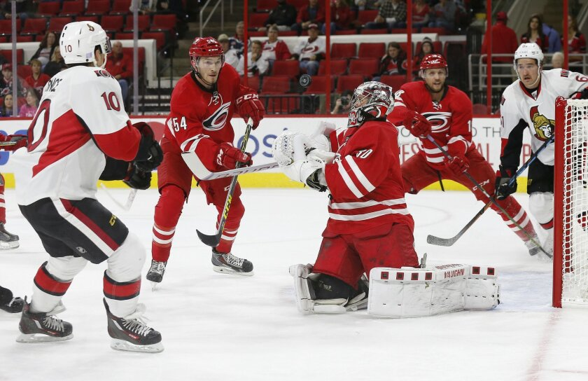 Carolina Hurricanes goaltender Cam Ward (30) makes a save on a shot by Ottawa Senators' Shane Prince (10) as Hurricanes' Brett Pesce (54), Jay McClement, second from right, and Senators' Mark Stone, right rear, look on during the first period of an NHL hockey game in Raleigh, N.C., Saturday, Nov. 7