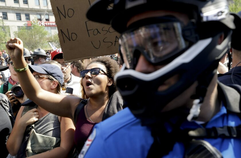 A Republican presidential candidate Donald Trump protester yells as a police officer stands by on at Public Square Tuesday, July 19, 2016, in Cleveland, during the second day of the Republican convention. (AP Photo/Patrick Semansky)