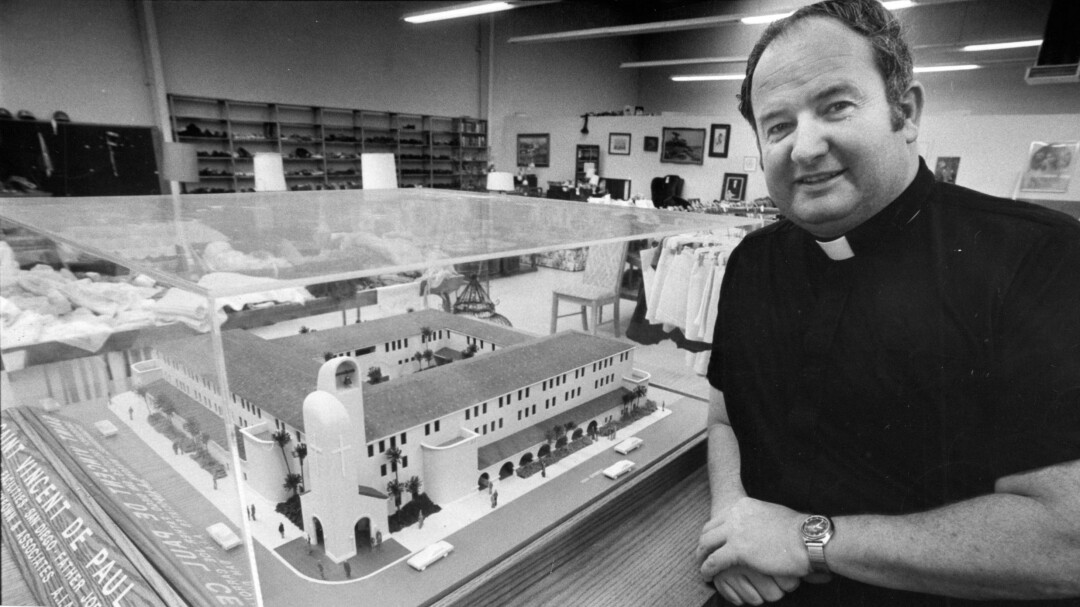 Father Joe Carroll stands with a model of the St. Vincent de Paul Center for the homeless