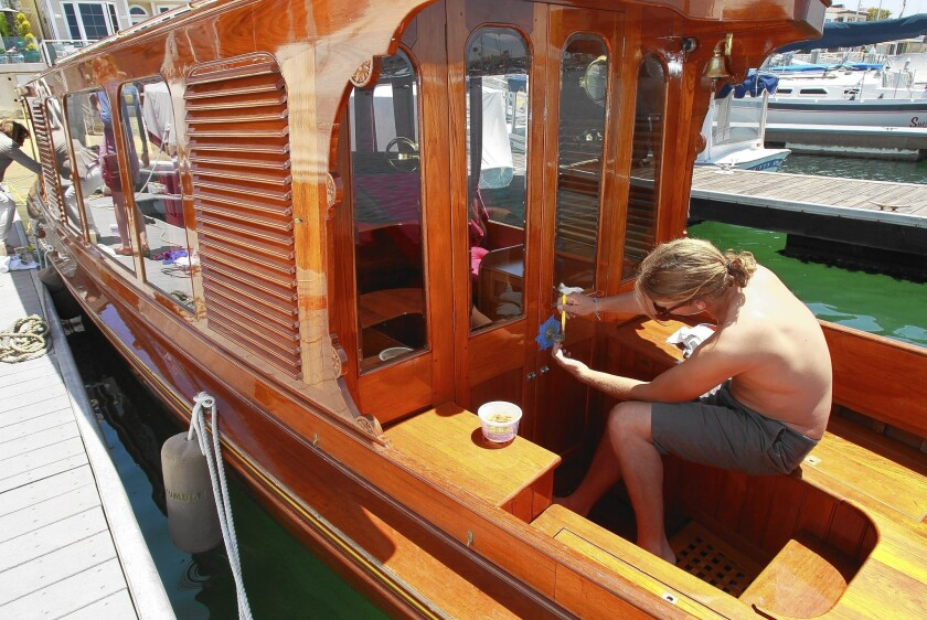 Victoria Fash's 1902 English Gentleman's Launch all wooden boat is cleaned up for Saturday's wooden boat festival at the Balboa Yacht Club in Newport Beach. A worker cleans the all brass handles after a varnish was put on the mahogany wood over the last week.