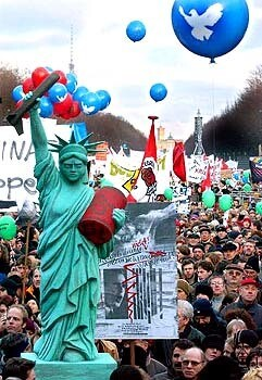 A mock Statue of Liberty carrying a missile and an oil drum is carried through the streets of Berlin.