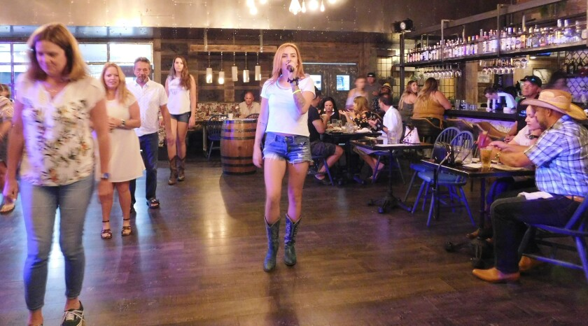 Aleigha Elston, center, teaches free line dancing and country partner dancing to Barn customers.