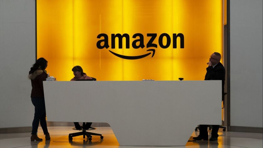 FILE - In this Feb. 14, 2019 file photo, people stand in the lobby for Amazon offices in New York. A